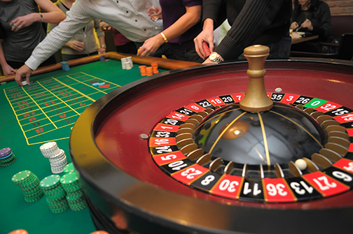 picture of players hands, roulette and piles of chips on a green table