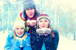 Winter family outdoors. Happy joyful family with kid blowing snow